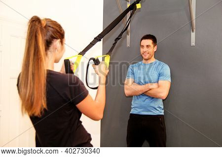 Beautiful Pretty Fitness Sporty Woman With Help Of Her Personal Trainer Exercising With A Resistance