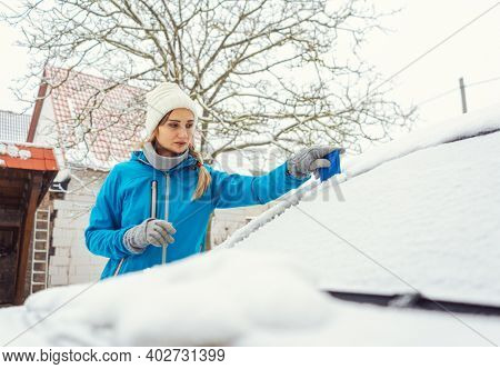 Woman scraping off ice from front window of her car in winter being a bit annoyed