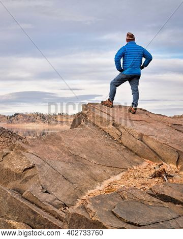 male hiker on a rocky cliff  at foothills of Rocky Mountains, Horsetooth Reservoir area - a popular recreational area in northern Colorado in fall or winter scenery