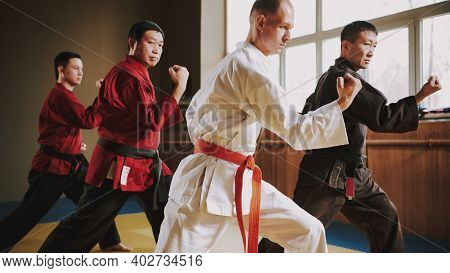 A Man In A White Kimono Finishes Off An Opponent Who Lies On The Floor. Fight Of Men Who Practice Ka