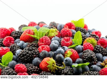 Berries. Various colorful berries background. Mint leaves, Strawberry, Raspberry, Blackberry, Blueberry close-up backdrop, isolated on white