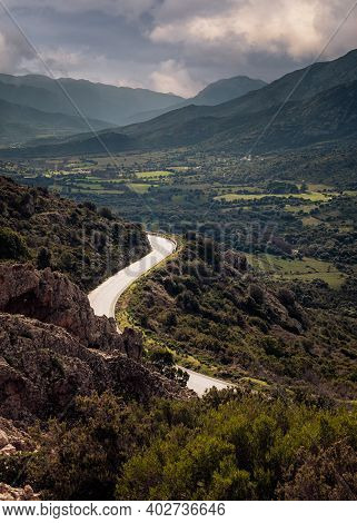 A Road Winds It's Way Down Towards The Lush Green Valley Of The Calenzana-moncale Forest Near Calvi