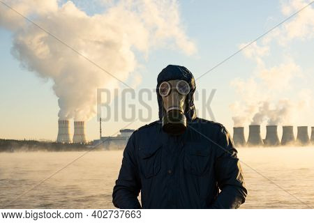 A Human In A Gas Mask Stands Against The Background Of A Nuclear Power Plant That Emits Chemicals In