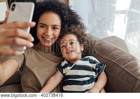 Young Mother And Her Little Son Spending Time Together. Happy Boy Taking A Selfie With His Mother.