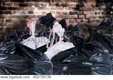 Rubbish Trash Bags Ready For Collection Against An Old Brick Wall. Household Refuse Collection Sacks