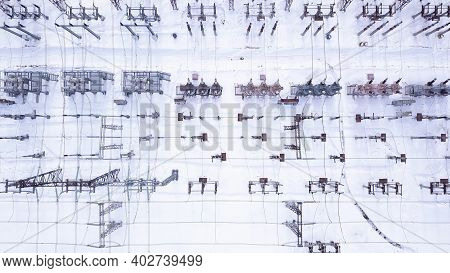 Rows Of Electric Poles. Action. Top View Of Electrical Substation With Rows Of Transformers In Winte