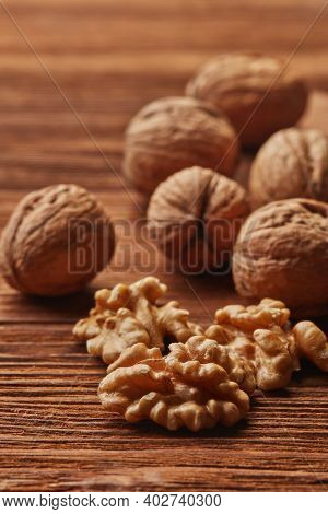 Still life from whole walnuts and walnuts kernels on brown textured wooden background. Selective focus on kernels. Healthy food. Vegetarian food