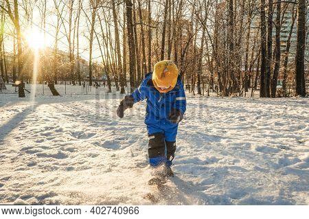 Boy Kicking Snow In Winter, Park. Sunny Day.