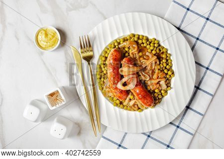 English Meal On A White Plate: Roasted Pork Sausage With Green Peas And Classic Onion Gravy On A Whi