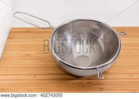 Empty Round Stainless Steel Sieve With Wire Mesh In Stainless Steel Bowl On A Wooden Surface On A Wh