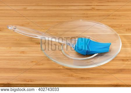 Pastry Brush With Blue Silicone Bristles And Transparent Plastic Handle On A Glass Saucer On A Woode