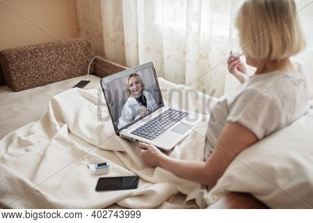 Old Woman In Bed Looking At Screen Of Laptop And Consulting With A Doctor Online At Home, Telehealth