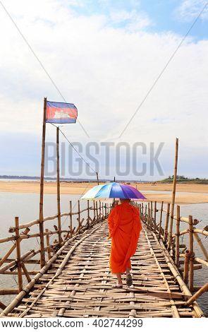 Buddhist monk with rainbow umbrella on bamboo bridge across Mekong river between Kampong Cham city and island of Koh Paen, Cambodia