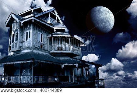Haunted house. Old abandoned house on night sky background. Scary colonial cottage in mysterious landscape. Photo toned in blue color