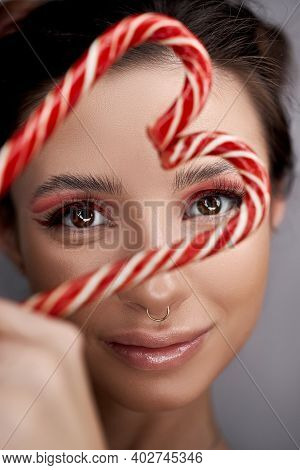 Bright Red Eye Makeup Woman Close-up With Caramel In Her Hands, Beautiful Even Eyebrows And Long Eye