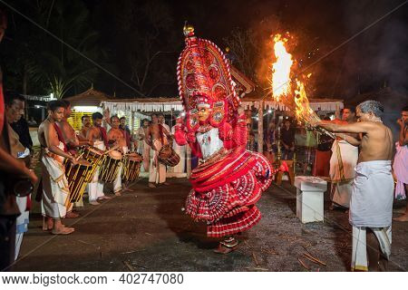 Payyanur, India - December 5, 2019: Theyyam artist perform with fire during temple festival in Payyanur, Kerala, India. Theyyam is a popular ritual form of worship in Kerala, India