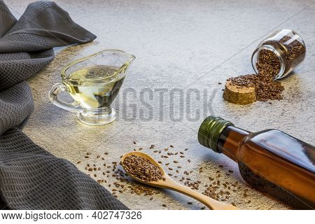 Linseed Oil In Glass Gravy Boat And Bottle, Flaxseed In Wooden Spoon And Jar, Vegetable Source Of Om