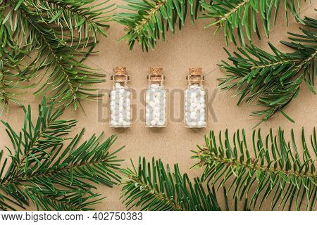 Homeopathic Pills In Glass Bottles Pine Tree Close Up. Homeopathy, Naturopathy And Alternative Medic