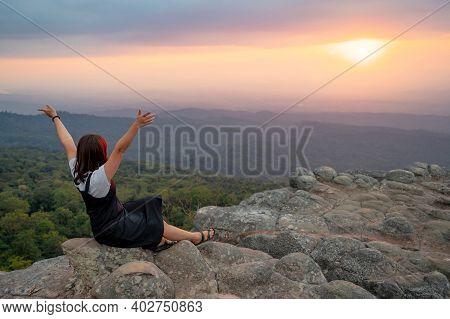 Achievement Concept. Asian Woman Raising Hands Sitting On Nodule Rock Field Called Lan Hin Pum Enjoy