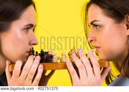 Dark-haired Young Women In Blue Dress Play Chess On Studio Yellow And Black Background