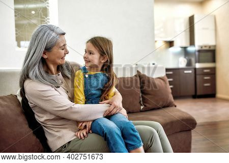 Portrait Of Loving Grandmother And Adorable Sweet Granddaughter Looking At Each Other With Tender An