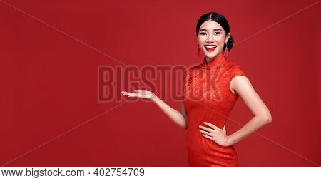 Happy Chinese New Year. Asian Woman Wearing Traditional Cheongsam Qipao Dress With Gesture Of Introd