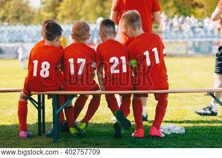 Young Soccer Team Sitting On Wooden Bench. Young Football Players. Soccer Match For Children. Young