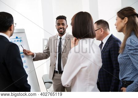 Group of multy-ethnic business people having a meeting using a white board in an office together