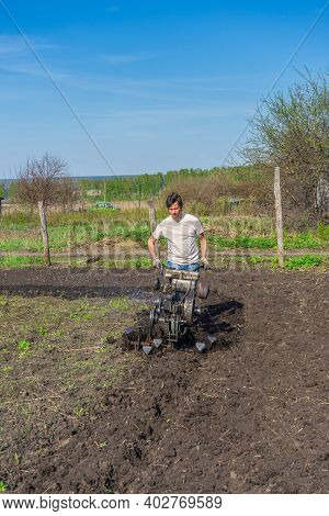 Man In Wellingtons With Cultivator Ploughs Ground In Sunny Day. Land Cultivation, Soil Tillage. Spri