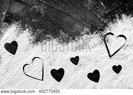 Heart Shapes Different Size Made Of Flour On Dark Board Or Table, Top View. Space For Text. Valentin