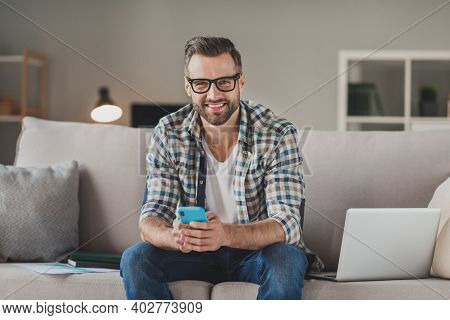 Photo Of Young Cheerful Handsome Man Happy Positive Smile Sit Sofa Indoors Chat Type Sms Browse Cell