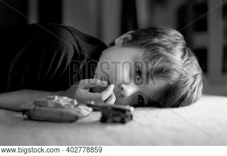 Black And White Photo Of Lonely Boy Laying Down On Floor Looking Out Deep In Thought, Sad Kid Laying