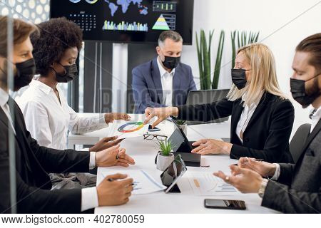 Confident Experienced International Team Of Business Colleagues In Protective Masks, Working Togethe