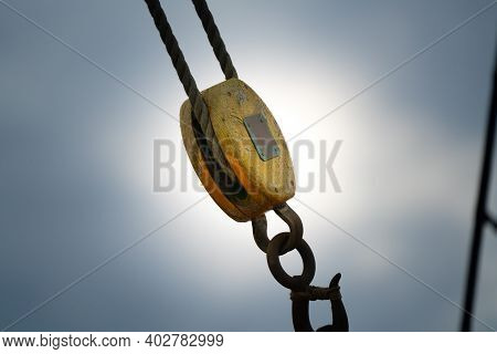 Old Wooden Pulley And Metal Hook Mountain On A Classical Sailboat.