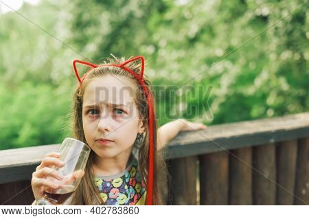 Girl Drinks From A Glass In A Summer Street Cafe. Leisure In The Cafe.