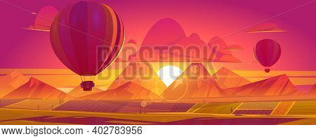 Hot Air Balloons Flying Above Fields, Mountains In Red And Orange Colored Sky On Sunset Or Sunrise S