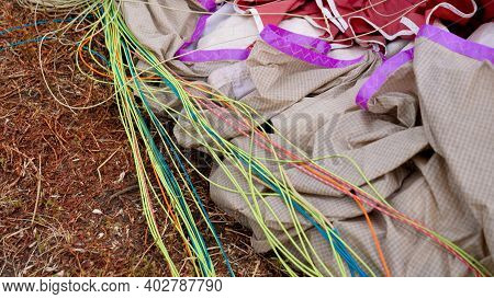 Closeup Of Straps, Parachute And Backpack Lying On Grass Field After Sky Diver Landing On Field. Con