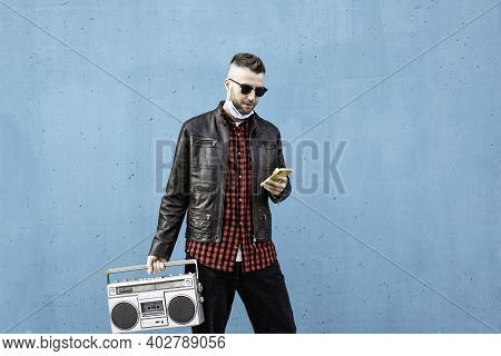 Hipster Man Using Yellow Smartphone While Listening Music With A Vintage Boombox Player Against A Bl