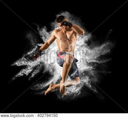 MMA male fighter jumping with a knee kick. White smoke background
