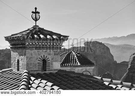 Domes with crosses of Varlaam orthodox monastery and Meteora rocks in the background, Greece. Black and white greek landscape