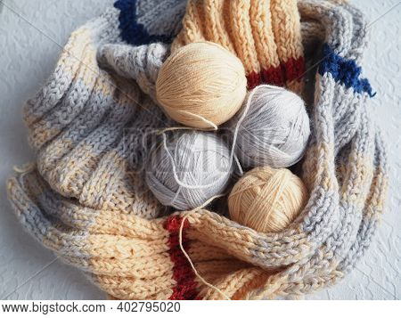 Knitting A Scarf Or Sweater From Yarn Of Different Colors. Balls Of Woolen And Acrylic Threads. Knit