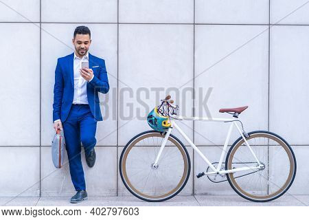 Young Latino Businessman Using Cellphone Outdoors.