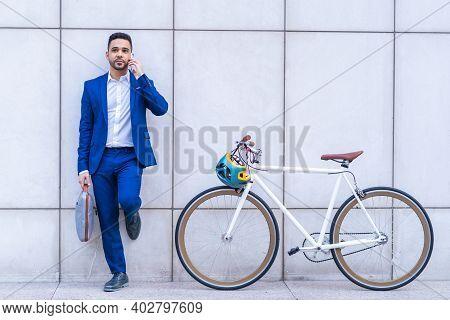 Young Latino Businessman Having Phone Call Outdoors.