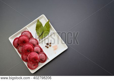 Red Frozen Homemade Dumplings And Spices In A Square Plate On A Gray Background. Homemade Semi-finis