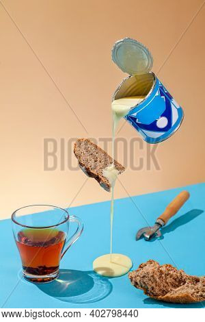 Puddle Of Condensed Milk Flows From Levitating Jar, Can Opener, Black Bread, Glass Of Black Tea