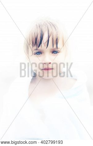 A Beautiful Little Angel Girl With Fathomless Blue Eyes. Portrait Of An Innocent Child In A White Ha