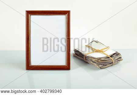 Blank Photo Frame For Photos, Flower In A Pot, Stack Of Old Photos On The Table.mockup.