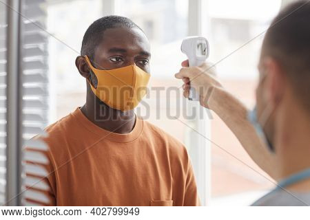 Portrait Of Adult African-american Man Wearing Mask Getting Temperature Check While Waiting In Line