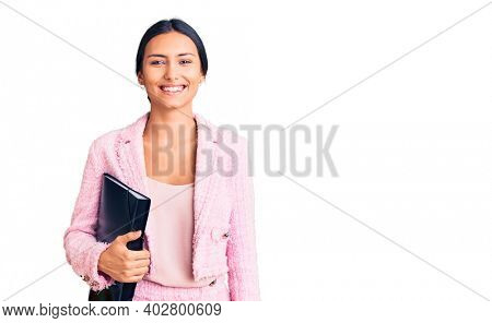 Young beautiful latin girl wearing business clothes holding binder looking positive and happy standing and smiling with a confident smile showing teeth