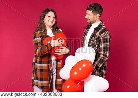 Cute Couple With Red Heart Balloons Smiling And Posing On A Red Background. St Valentines Day.